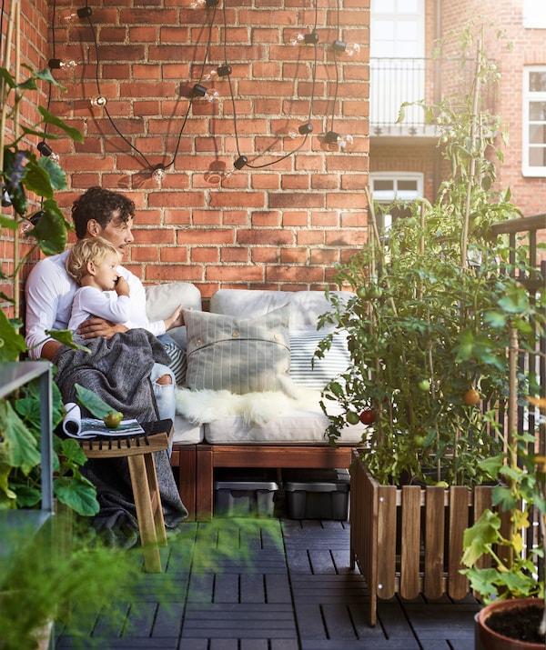阳台上,大人和小孩正坐在一条长椅上,旁边是一面红色砖墙。