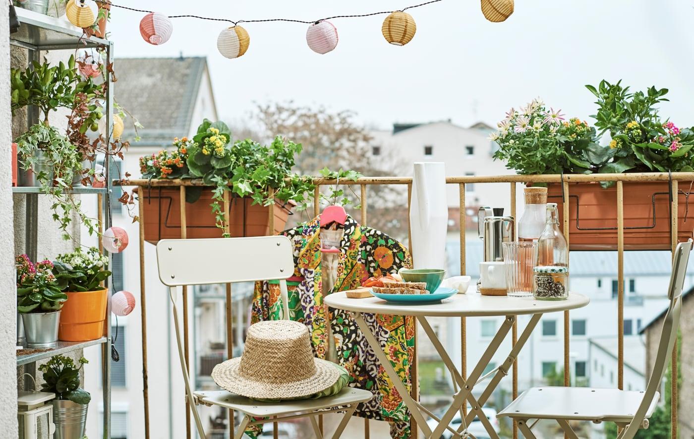 阳台上带有花箱、摆放植物的搁架单元、灯串和小餐馆风格餐具,桌上摆放有零食。