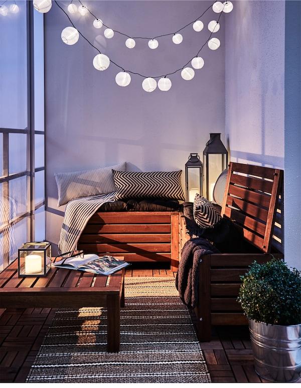 阳台温馨舒适的小角落里挂着灯串,旁边摆放着一些纺织品。