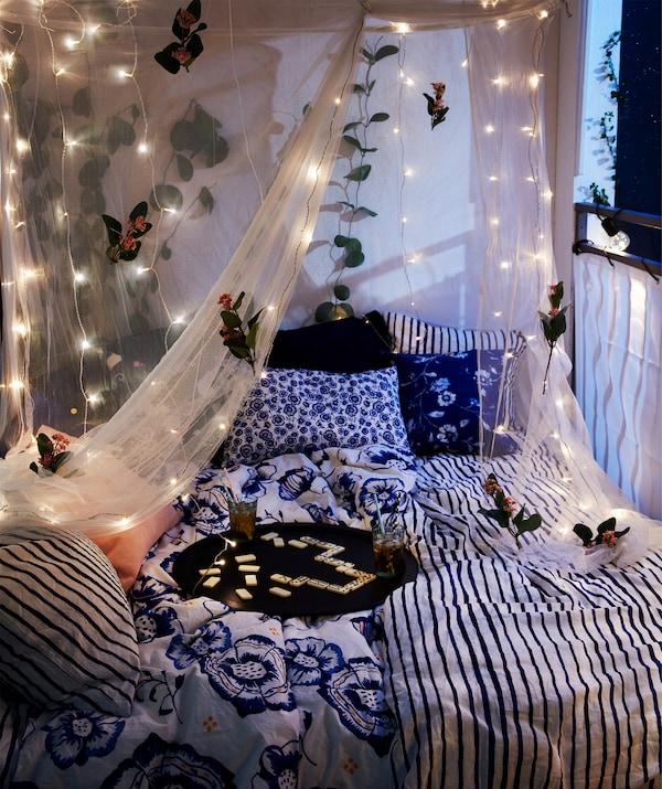 夜间,阳台上放置着一张双人床,上面摆放着一个盛有饮料的托盘,挂有灯串的帘帐罩在上方。