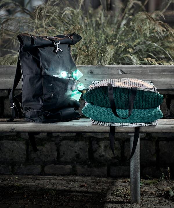 夜晚时分,一张公共长椅上放着一个背包,包里的小彩灯亮了起来,还有一包纺织品。