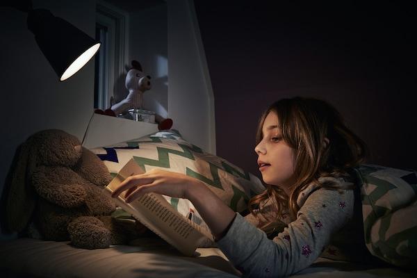 夜晚,小女孩穿着睡衣躺在床上,借着夜照明灯的光看书。