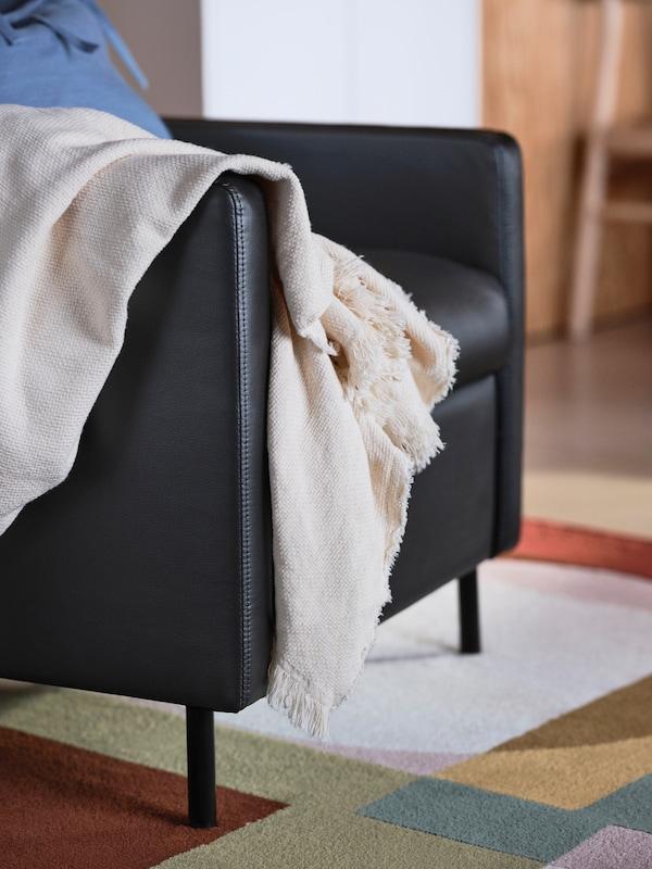 一把黑色GISTAD 基斯塔 躺椅立在一块色调明快的多彩地毯上,一条米色毯子从一侧扶手上垂落。