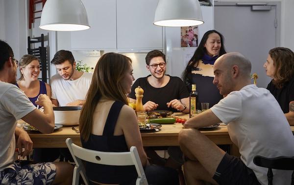 一大群人围坐在桌边用餐、聊天。