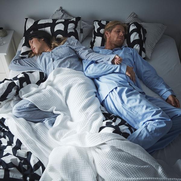 一对夫妇穿着情侣睡衣,躺在一张双人床上熟睡。
