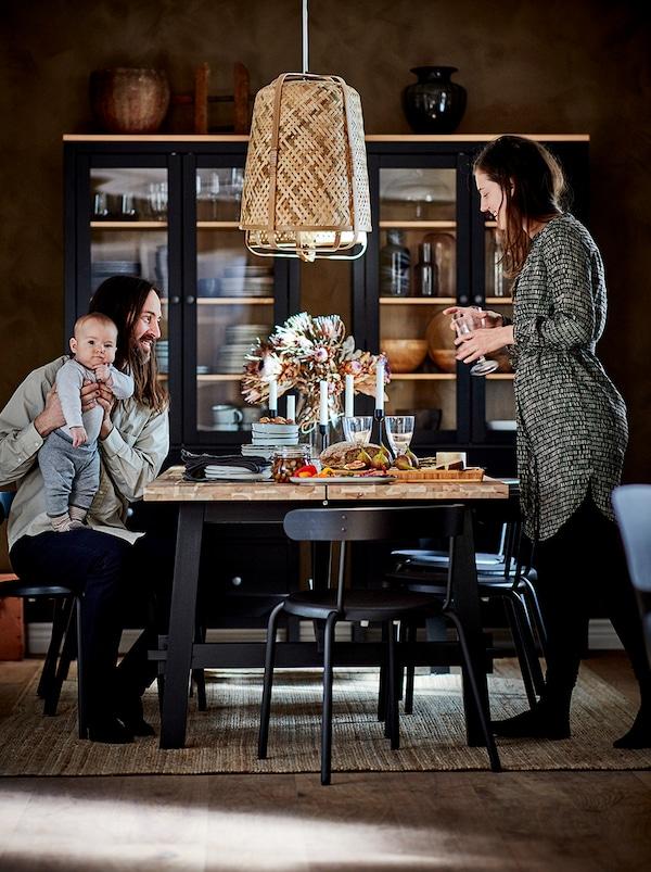一对夫妇和他们的宝宝围在一张餐桌旁边。墙壁旁有一个深色玻璃门柜,里面存放着餐桌用具。