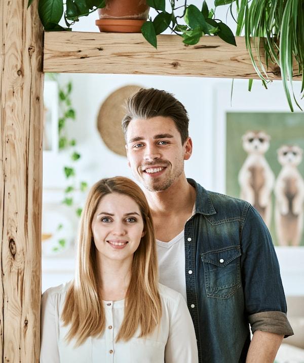 一对年轻夫妇站在木梁旁边,身后的墙上挂着带框图片。