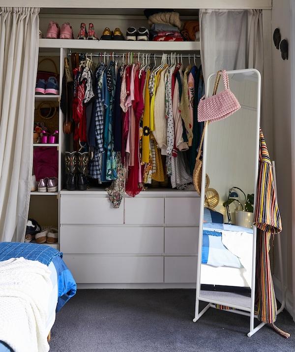 衣服挂在挂杆上,鞋子放在搁板上,搁板下方有两个抽屉柜,两边配有挂帘,同时还有一个独立式立镜。