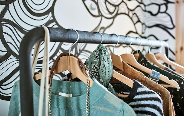 衣服挂在挂衣杆的木制外套挂架上,挂衣杆后面是波浪形的黑白墙纸。