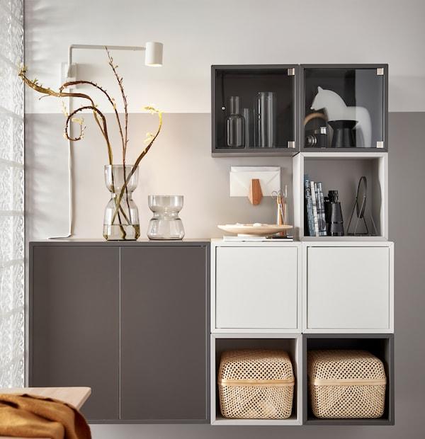 一个白色和灰色的EKET 伊克特 储物单元组合,带两个SMARRA 斯马拉 储物盒、两个玻璃花瓶和一些装饰品。