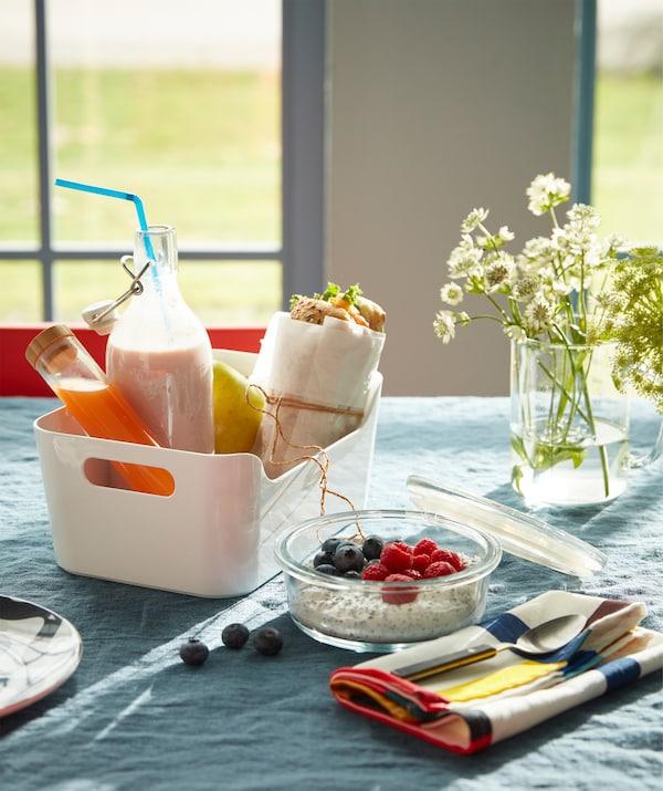 一个白色 VARIERA 瓦瑞拉 盒子内装有一个三明治、一杯玻璃瓶酸奶和一份果汁,组成了外卖风早餐。