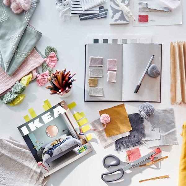 一个笔记本、一支笔、剪刀、几块粉色、灰色、黄色、绿色和芥末黄色布料,旁边是一本2021年宜家《家居指南》。