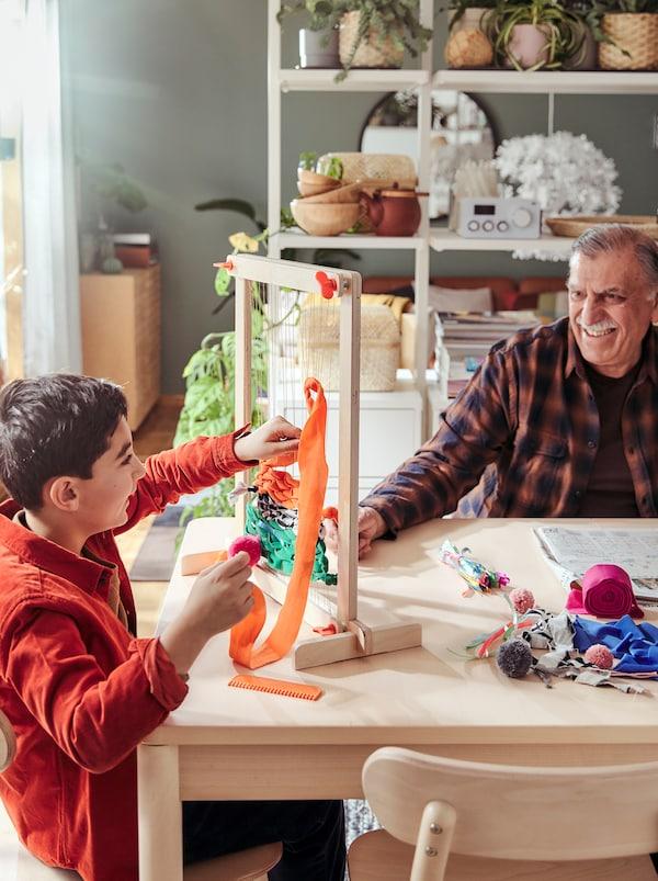 一个成年男人和一个小男孩坐在桌子两边,微笑地看着对方,桌子上放着一台LUSTIGT 卢斯蒂格 织布机。