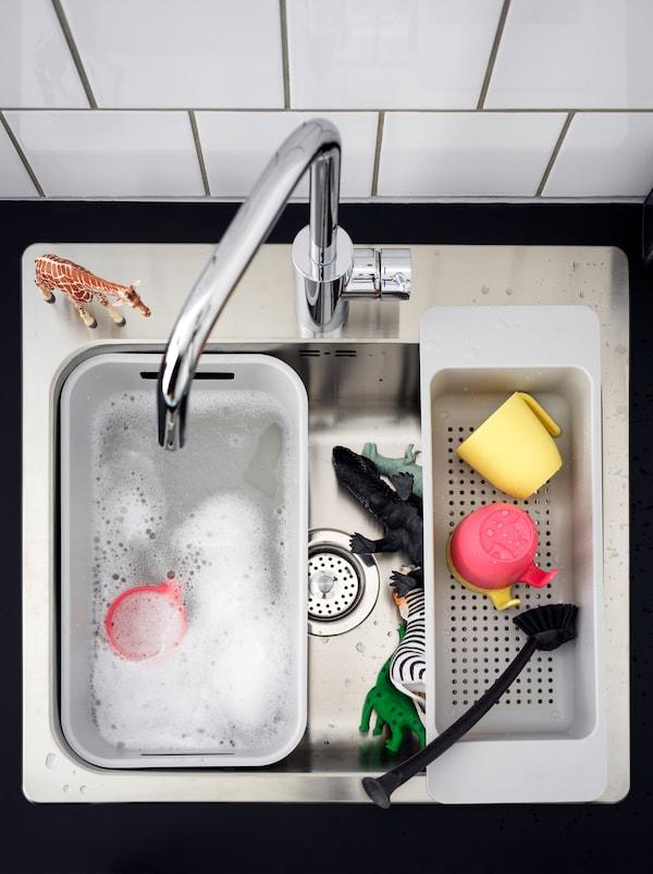 一个厨房水槽,配一个白色的GRUNDVATTNET 伦瓦特 洗碗槽,里面装着肥皂水,旁边还有一些玩具动物。