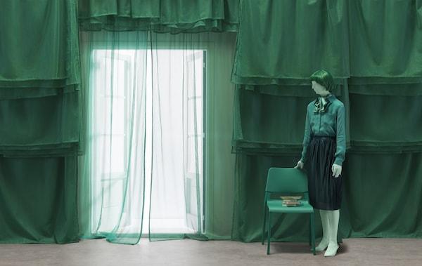 一个穿着绿衣服的人坐在低抽屉柜上,旁边是带有抽屉且挂有衣物的高抽屉柜。