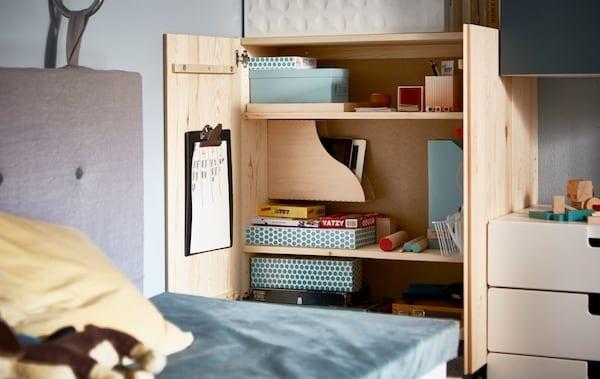 一个打开的 IVAR 伊娃 储物柜,里面整齐地装着游戏用品和文件盒。