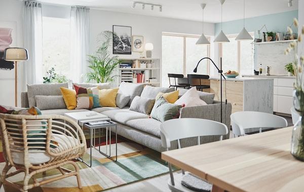 一个大房间里,带有厨房多用桌的厨房区,旁边是摆放着宽敞转角沙发的客厅区。