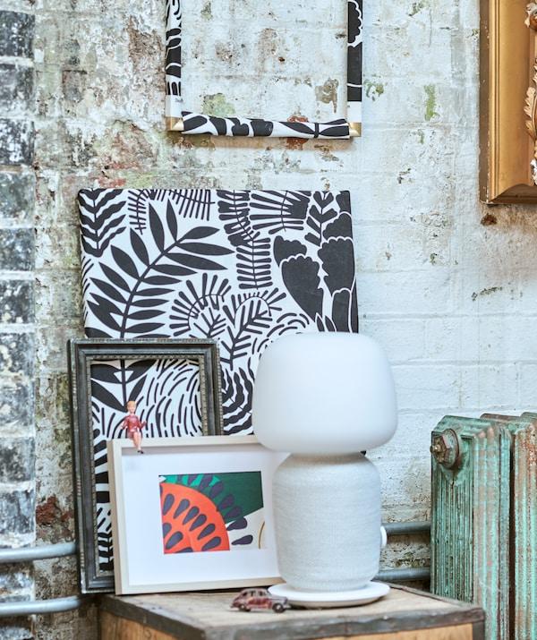 一个带白色音箱照明的茶箱上展示着饰有图案的布料,它们采用不同的方式装裱并倚靠着砖墙摆放。