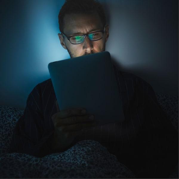 一个戴眼镜的男士正躺在床上翻看平板电脑,散发出的光线映出他疲惫不堪的脸庞。