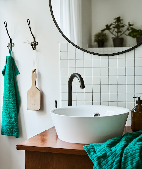一个独特的洗脸池柜搭配圆形白色现代水槽和复古桌子,旁边是复古瓷砖和黑色圆镜。