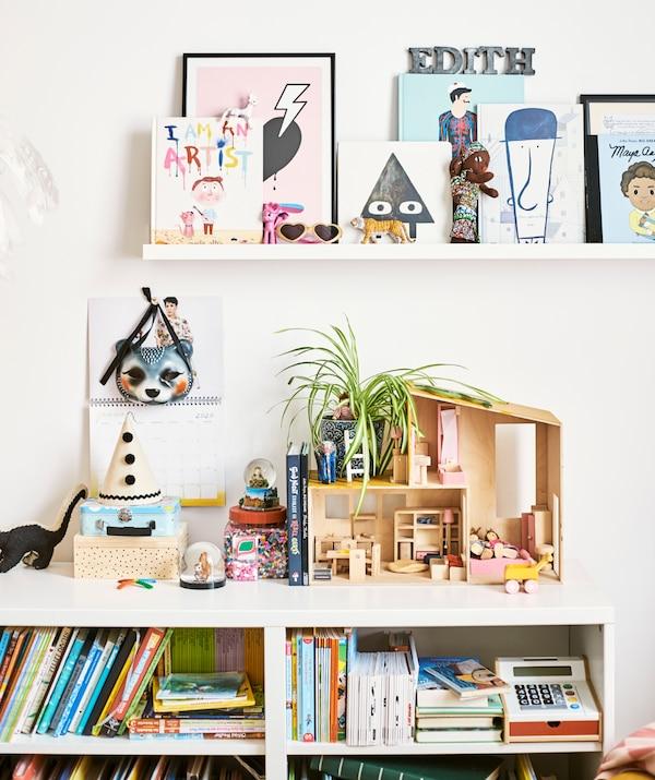 一个儿童书柜里装满了书本和游戏,最上面是玩偶屋和玩具盒,墙上的搁板上放着书本。