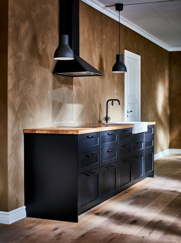 一个改造中的黑色调厨房,搭配深灰色的HEKTAR 赫克塔 吊灯、黑色水龙头和白色HAVSEN 霍夫森 水槽,水槽前侧显露了出来。