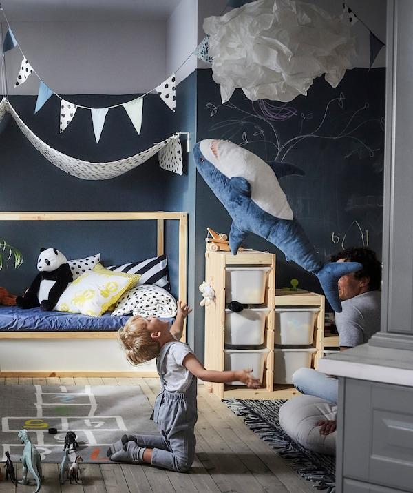 一个孩子把鲨鱼毛绒玩具抛向空中,后方是储物盒和布艺凉篷。