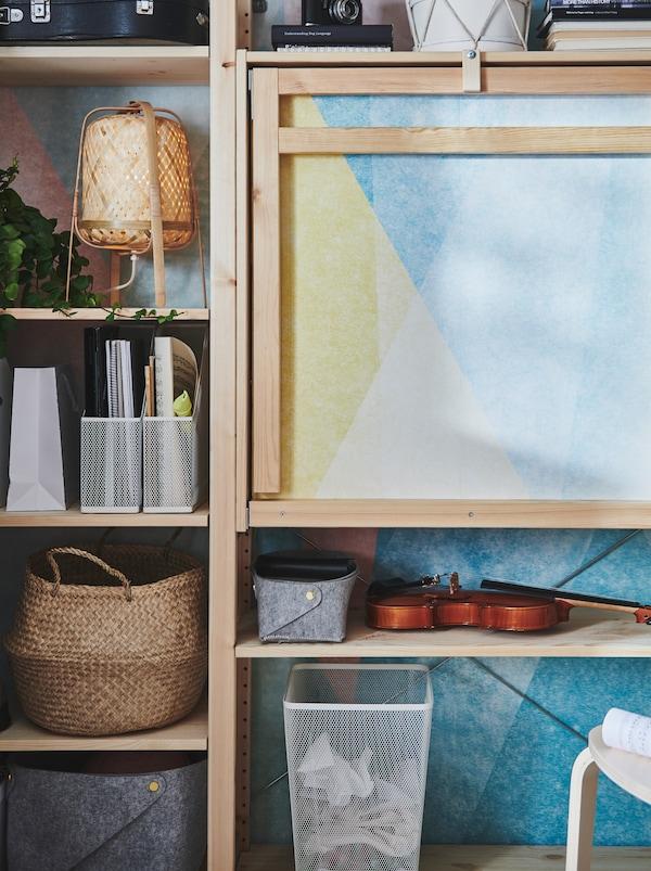 一个IVAR 伊娃 储物单元,带折叠桌,采用未经处理的木材制成,搁架上摆放着各种金属、藤和毛毡材质的物品。