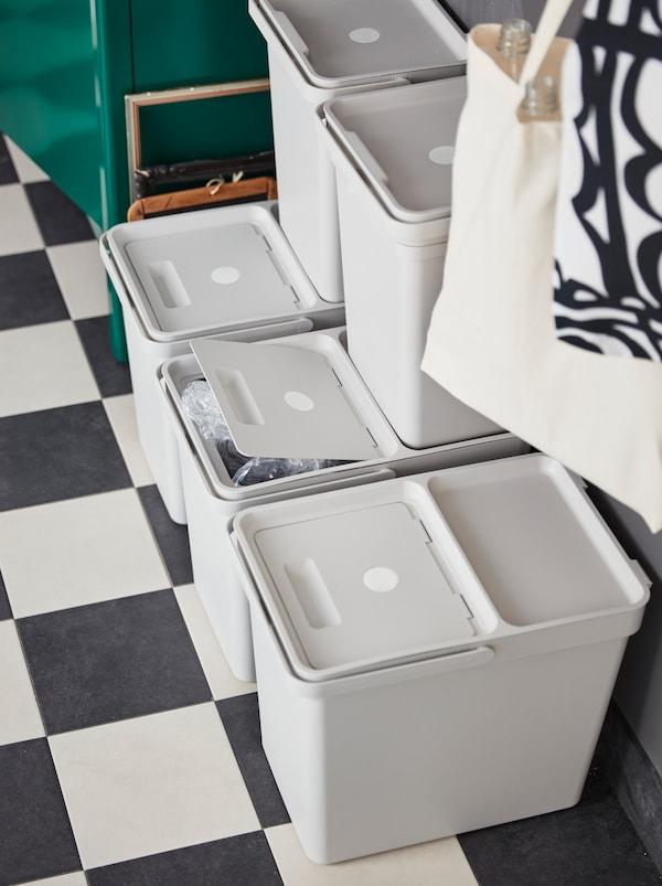 一个角落里,五个带盖的浅灰色HÅLLBAR 哈尔巴 垃圾桶叠放在一起,用于废品处理和分类回收。