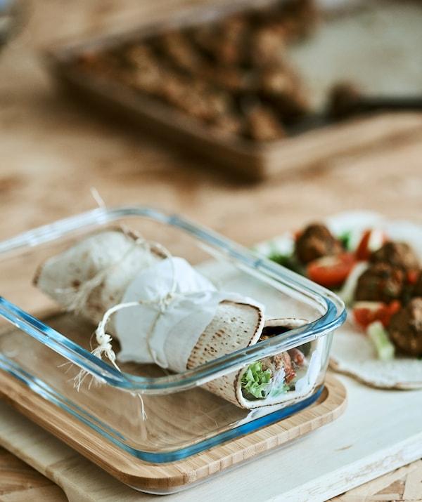 一个卷好的墨西哥玉米薄饼放在玻璃容器中,旁边是一张摊开的墨西哥玉米薄饼,上面放了馅料。
