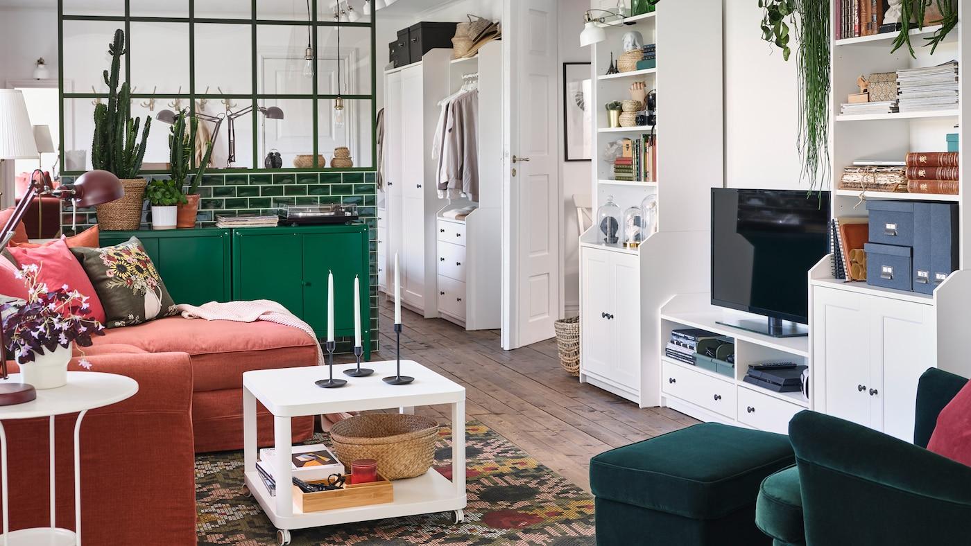 一个客厅,有一张深绿色的靠背椅和脚凳,绿色的柜子和白色的HAUGA 豪嘉 视听储物组合。