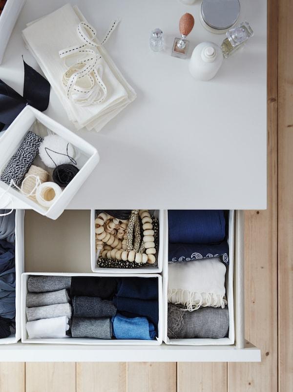 一个拉开的卧室抽屉,其中摆放着几个白色SKUBB 思库布 储物盒,里面装有项链、折叠得整整齐齐的袜子和围巾。