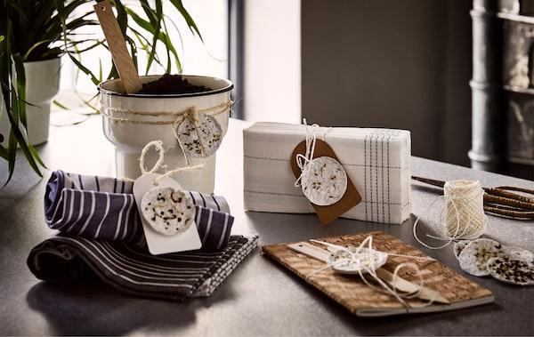 一个米色花盆、一本棕色笔记本、一叠纺织餐巾和餐巾纸上系着自制种荚。