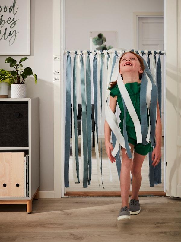 一个面带微笑、头往后仰的小女孩经过饰有 DITTE 迪特 布料、悬挂在门口的 BOTAREN 博塔仁 浴帘杆。