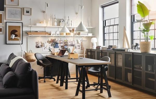 一个木制的工作桌上有台灯、纸张和笔