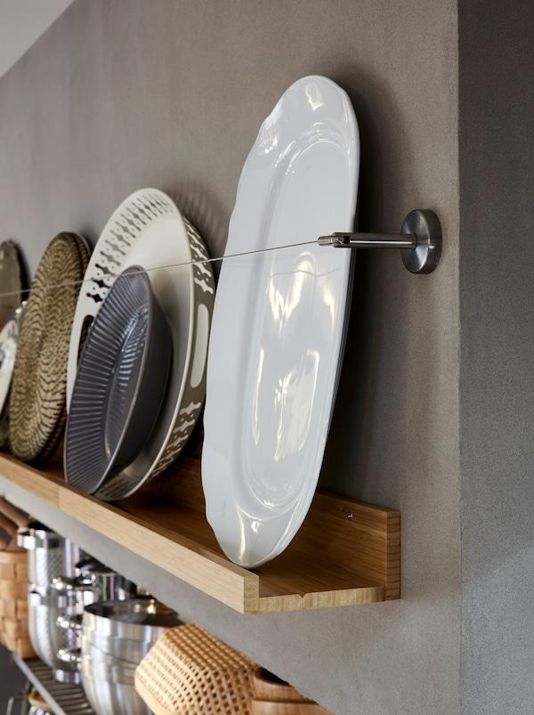 一个木制MÅLERÅS 摩乐若思 壁式图片架上,展示着盘子和其他扁平的厨房用品,搭配一根金属窗帘挂线,提供保护。