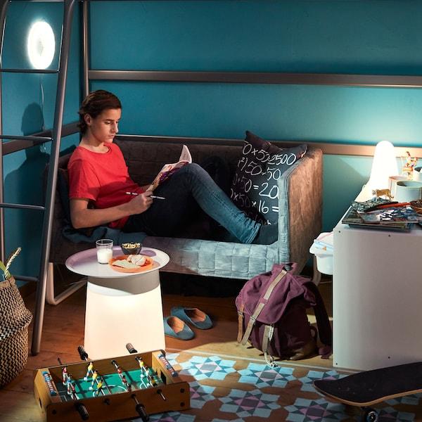 一个男孩坐在小沙发上做家庭作业。一张高架床下摆着一张沙发。