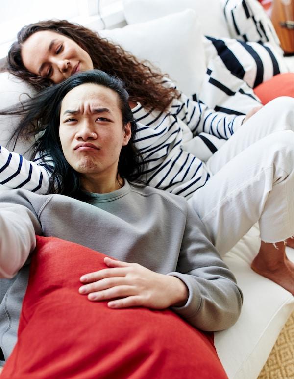 一个男人和一个女人坐在白色的沙发上,四周摆满了黑白条纹和彩色的靠垫。