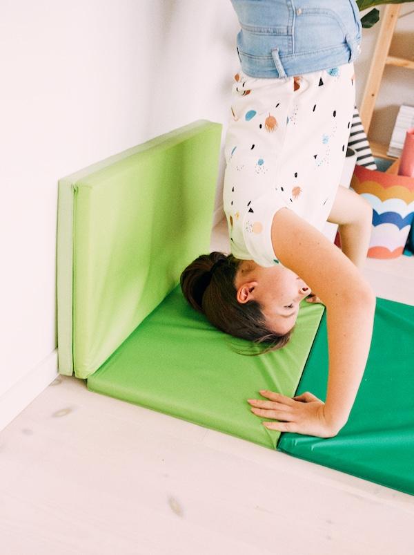一个年轻女孩在墙边倒立,手和头撑在亮绿色的 PLUFSIG 普鲁希 可折叠健身垫上。