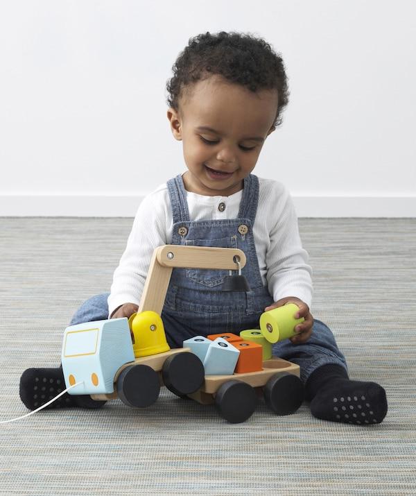 一个年幼的孩子在玩木制吊车和积木。