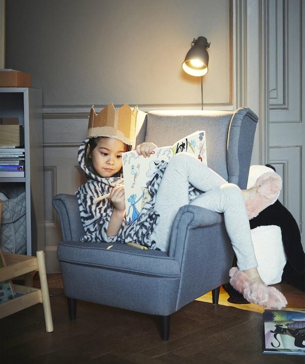 一个女孩戴着纸板做的皇冠,蜷缩在一把灰色椅子上涂色。