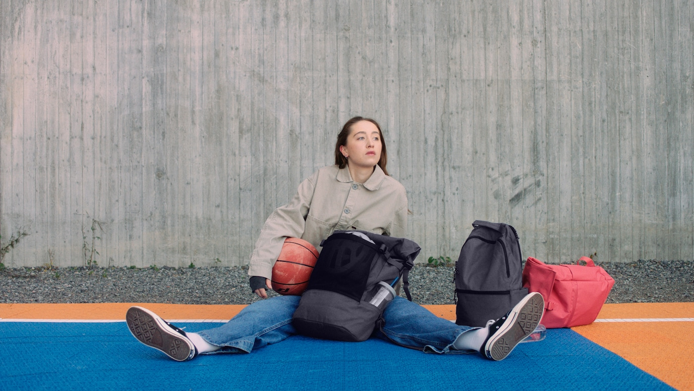 一个女孩拿着篮球,坐在篮球场上,身边放着 DRÖMSÄCK 德姆塞克、VÄRLDENS 维尔登斯 和 STARTTID 斯塔缇 包。