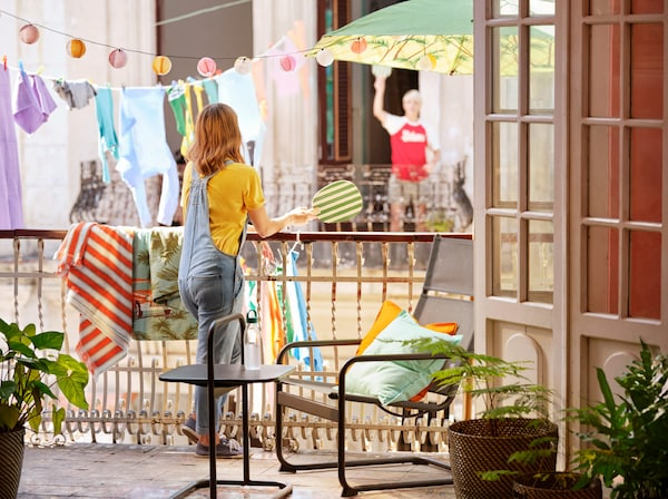 一个女孩拿着沙滩球拍,斜靠在阳台栏杆上。背后悬挂着灯具和衣物。
