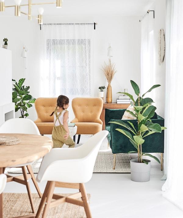 一个女孩跑着穿过一个开放式用餐/客厅区,其中摆放着绿色天鹅绒沙发、芥末绿休闲椅、白色的餐椅。