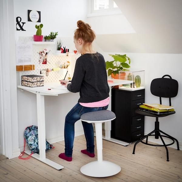 一个女孩坐在独立支撑椅上,在一张白色的升降桌旁做家庭作业。