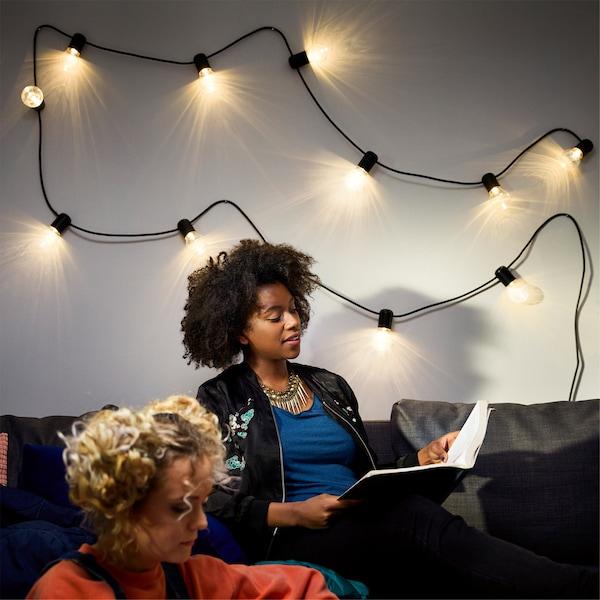 一个女孩坐在沙发上看书,身后的墙上挂着透明灯泡连成的灯串。