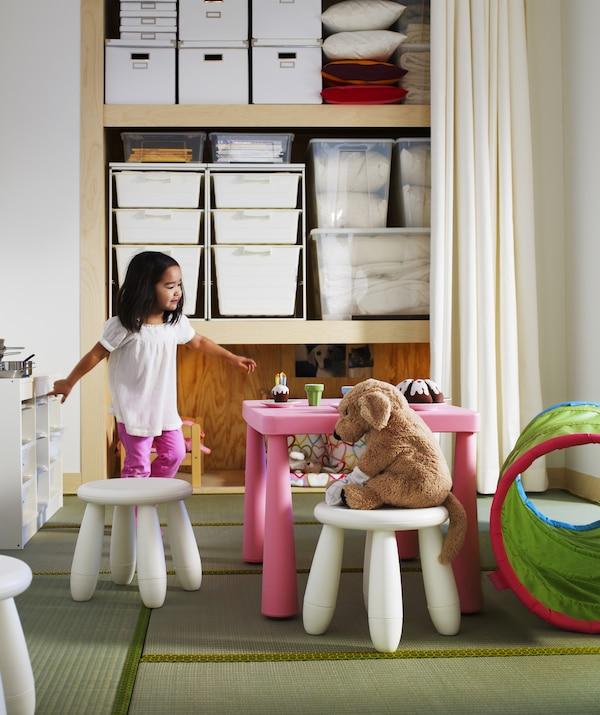 一个蹒跚学步的孩子正和毛绒玩具开茶话会,背后是一件开放式储物装置。