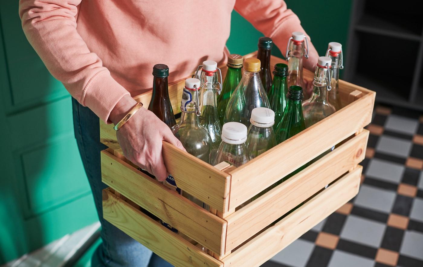 一个人提着装满各种杯子和塑料瓶的 KNAGGLIG 卡纳格 木储物箱穿过门厅。