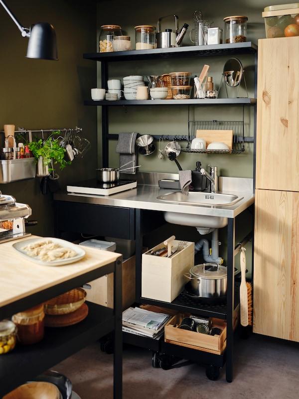 一个RÅVAROR 罗瓦露 迷你厨柜,配有悬挂的餐具滤干架和挂钩,上面摆满了餐具以及一个RÅVAROR 罗瓦露 储物盒。