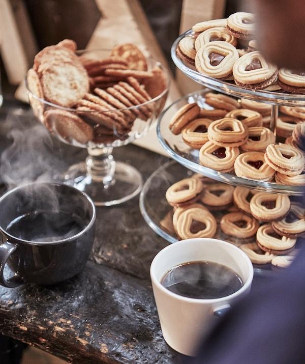 一个三层的盘中摆放着心形饼干,两杯热咖啡和一碗圆形饼干。
